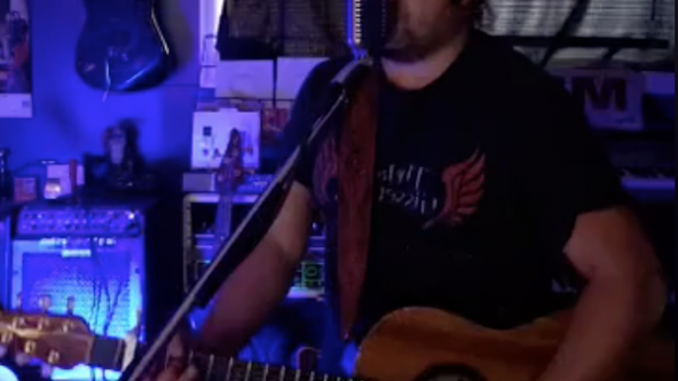 Jason Gisser Playing his Guitar and Singing